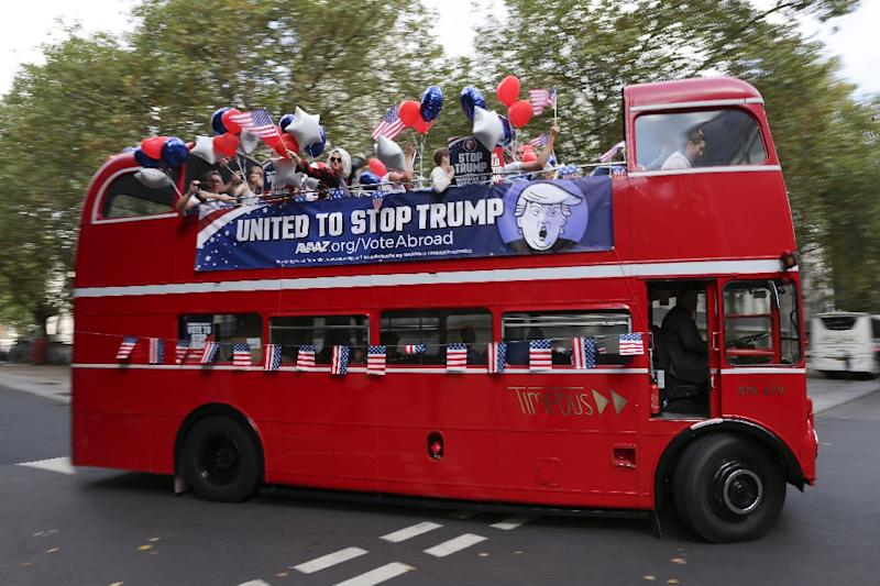 """Activists ride on a """"Stop Trump"""" bus in London on September 21, 2016 in a campaign to mobilise US expatriots to register to vote in the US presidential election"""