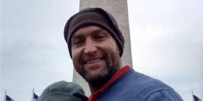 Landon Copeland posing in front of the Washington Monument with a woman, whose face has been blocked out by the FBI.