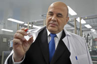 Russian Prime Minister Mikhail Mishustin holds a dose of the Russia-designed Sputnik V vaccine on a visit to production plant in Strelna near St. Petersburg. Russian authorities said that up to 300,000 people already have received a shot of the vaccine in St. Petersburg, Russia, Friday, Dec. 25, 2020. (Dmitry Astakhov, Sputnik, Government Pool Photo via AP)