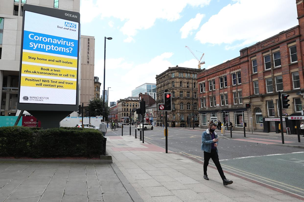 A person wearing a mask walks past Government advertising regarding coronavirus on a billboard in Manchester.