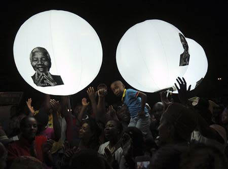 A boy looks on in front of balloons bearing a picture of former South African President Nelson Mandela on Vilakazi Street in Soweto, where Mandela resided when he lived in the township, December 7, 2013. REUTERS/Siphiwe Sibeko
