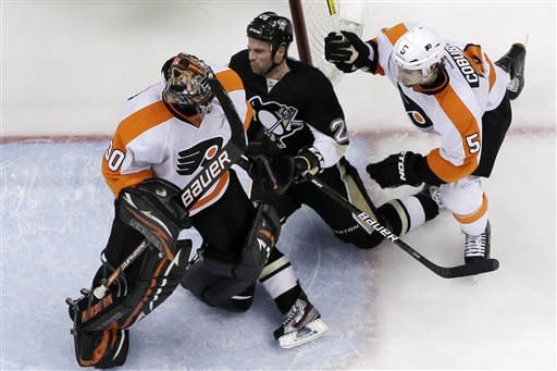 Philadelphia Flyers' Braydon Coburn (5) checks Pittsburgh Penguins' Steve Sullivan (26) into Flyers goalie IIya Bryzgalov (30) during the third period of Game 2 of an opening-round NHL hockey playoff series in Pittsburgh, Friday, April 13, 2012. The Flyers won 8-5. (AP Photo/Gene J. Puskar)