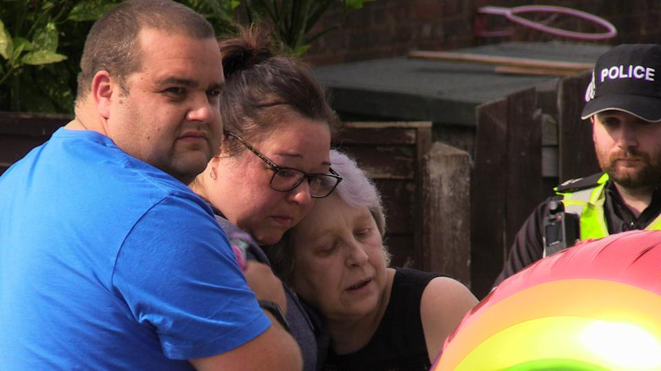People look at flowers near to the scene in Chandos Crescent, Killamarsh, near Sheffield, where the bodies of John Paul Bennett, 13, Lacey Bennett, 11, their mother Terri Harris, 35, and Lacey�s friend Connie Gent, 11, were discovered at a property on Sunday morning. Picture date: Tuesday September 21, 2021.