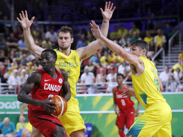 Munis Tutu of Canada looks to pass under pressure from Mitch Norton, left, and Damian Martin of Australia during the men's gold medal basketball game at the Gold Coast Convention and Exhibition Centre during the 2018 Commonwealth Games on the Gold Coast, Australia, Sunday, April 15, 2018. (AP Photo/Mark Schiefelbein)