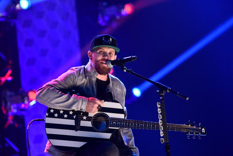 Brantley Gilbert poses for the camera while performing on stage and he looks breath