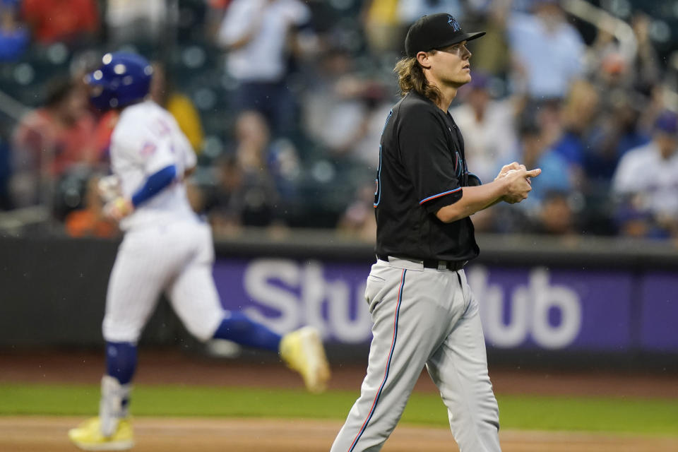 Miami Marlins relief pitcher Steven Okert, right, reacts as New York Mets' Francisco Lindor (12) runs the bases after hitting a two-run home run during the sixth inning in the first baseball game of a doubleheader Tuesday, Sept. 28, 2021, in New York. The Mets won 5-2. (AP Photo/Frank Franklin II)