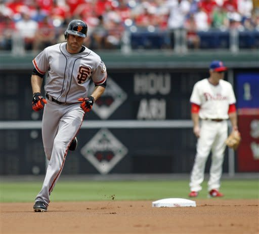 San Francisco Giants' Nate Schierholtz, left, runs the bases after he hit a solo home run against the Philadelphia Phillies in the first inning of a baseball game on Sunday July 22, 2012, in Philadelphia. (AP Photo/H. Rumph Jr)