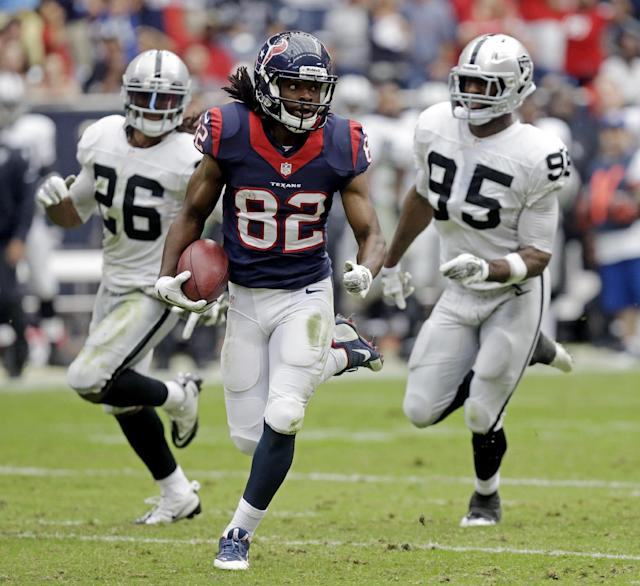 Houston Texans' Keshawn Martin gets past Oakland Raiders' Usama Young (26) and Kaelin Burnett (95) for an 87-yard touchdown on a punt return during the first half of an NFL football game Sunday, Nov. 17, 2013, in Houston. (AP Photo/Patric Schneider)
