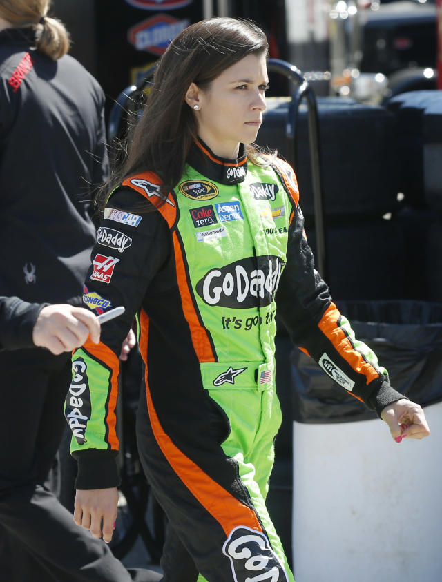 Driver Danica Patrick walks through the garage area before practice begin, Friday, May 9, 2014, at Kansas Speedway in Kansas City, Kan., for Saturday night's NASCAR Sprint Cup series auto race. (AP Photo/Orlin Wagner)