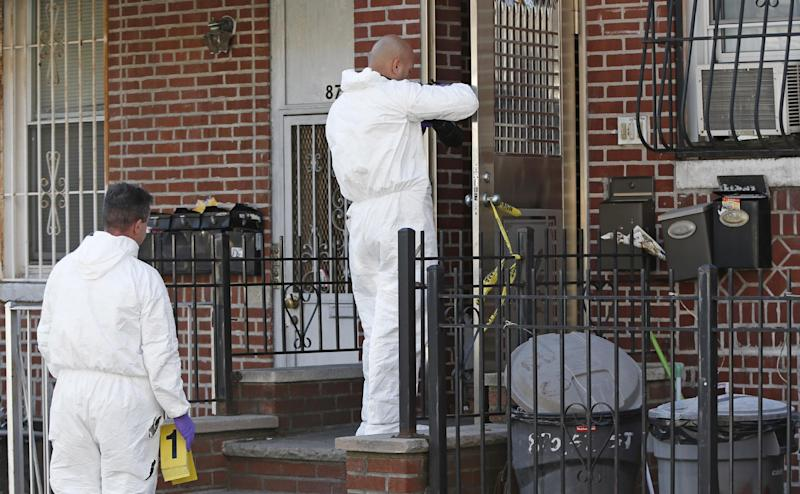 Crime scene detectives investigate the scene of a multiple fatal stabbing Sunday, Oct. 27, 2013, in New York. Police said a mother and her four young children were stabbed to death in a brutal rampage just before 11 p.m. Saturday in the Sunset Park neighborhood of Brooklyn. The New York Police Department said a suspect, 25-year-old Ming Don Chen, a Chinese immigrant, was arrested Sunday on five counts of murder in the deaths of his cousin's wife and her four children in the stabbing rampage in their Brooklyn home. (AP Photo/Kathy Willens)