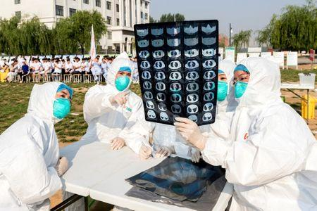 FILE PHOTO: People participate in an emergency exercise on prevention and control of H7N9 bird flu virus organised by the Health and Family Planning Commission of the local government in Hebi, Henan province, China June 17, 2017. Picture taken June 17, 2017. REUTERS/Stringer/File Photo