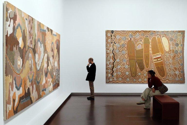 A man looks at the painting by Aborigine artist Clifford Possum Tjapaltjarri on October 9, 2012 in Paris