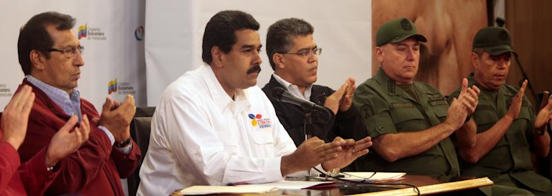 In this photo released by Miraflores Presidential Press Office, Venezuela's Vice President Nicolas Maduro, second from left, addresses the nation from Miraflores presidential palace during a meeting in Caracas, Venezuela, Tuesday, March 5, 2013.  At left is Governor Adan Chavez, the older brother of President Hugo Chavez. Maduro met with top Venezuelan government ministers, the military high command and all 20 loyalist governors in Caracas following word of Chavez's deteriorating health. Foreign Minister Elias Jaua sits third from right. (AP Photo/Miraflores Presidential Press Office)