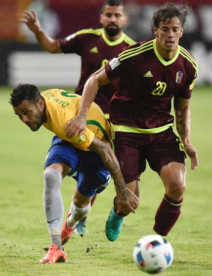 Brazil's Daniel Alves (L) fights for the ball with Venezuela's Rolf Feltscher during their Russia 2018 World Cup qualifier match in Merida, in October 2016 (AFP Photo/Juan Barreto)
