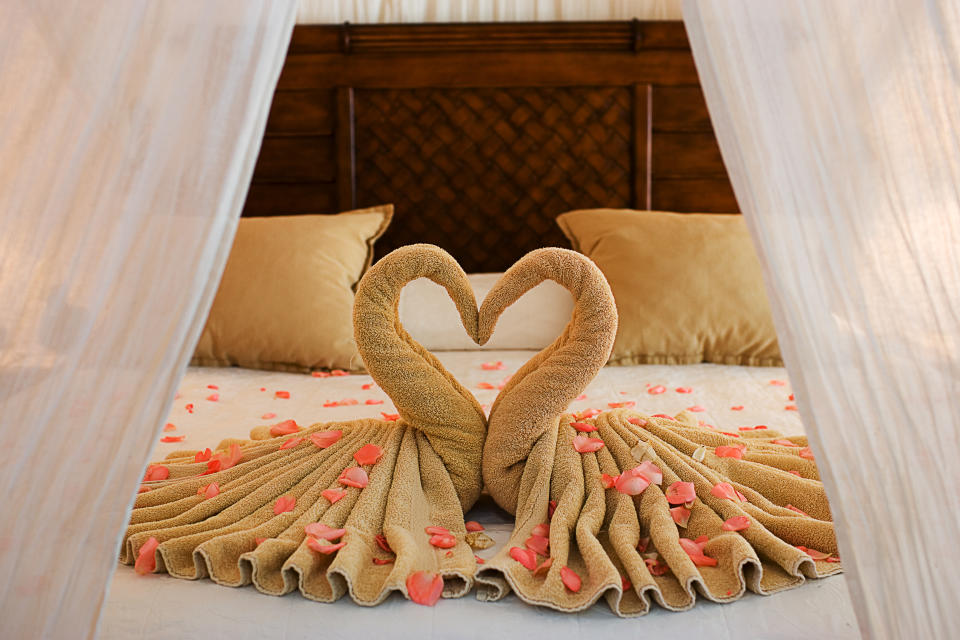 Beautiful Romantic Hotel Suite Interior with a pair of towel swans on the bed covered in rose petals