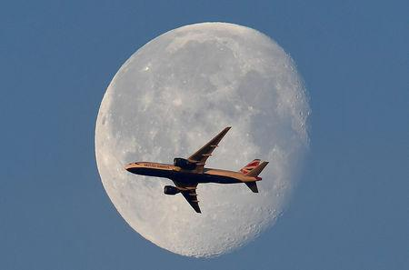 FILE PHOTO: A British Airways passenger plane flies in front of the moon above London, Britain, May 3, 2018. REUTERS/Toby Melville/File Photo