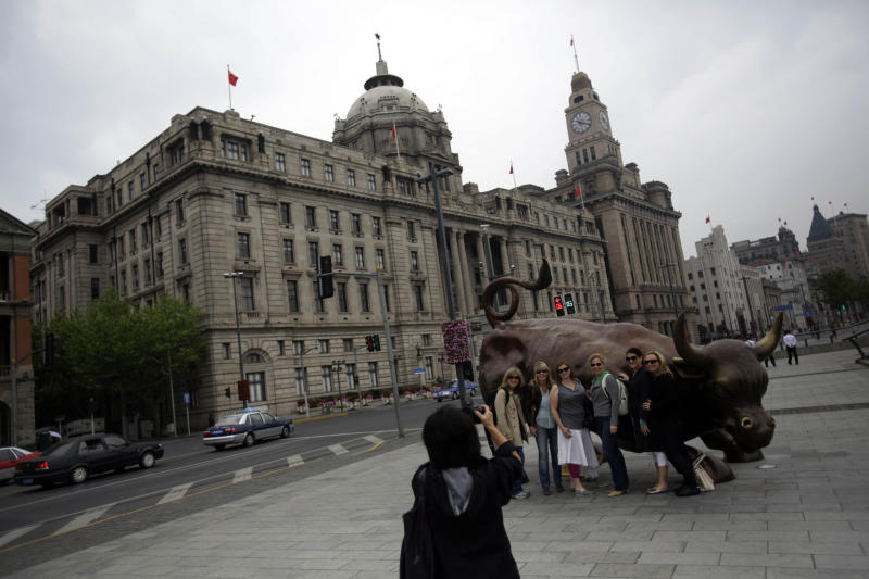 In this May 8, 2013 photo, tourists stroll on the the Bund, one of the most famous tourist destinations, in Shanghai, China. The avenue is lined with art deco buildings from the 1920s and '30s, when Shanghai was the New York of the Far East. The Bund was its Wall Street, home to international banks and trading houses where a handful of foreign and Chinese entrepreneurs made fortunes. (AP Photo/Eugene Hoshiko)