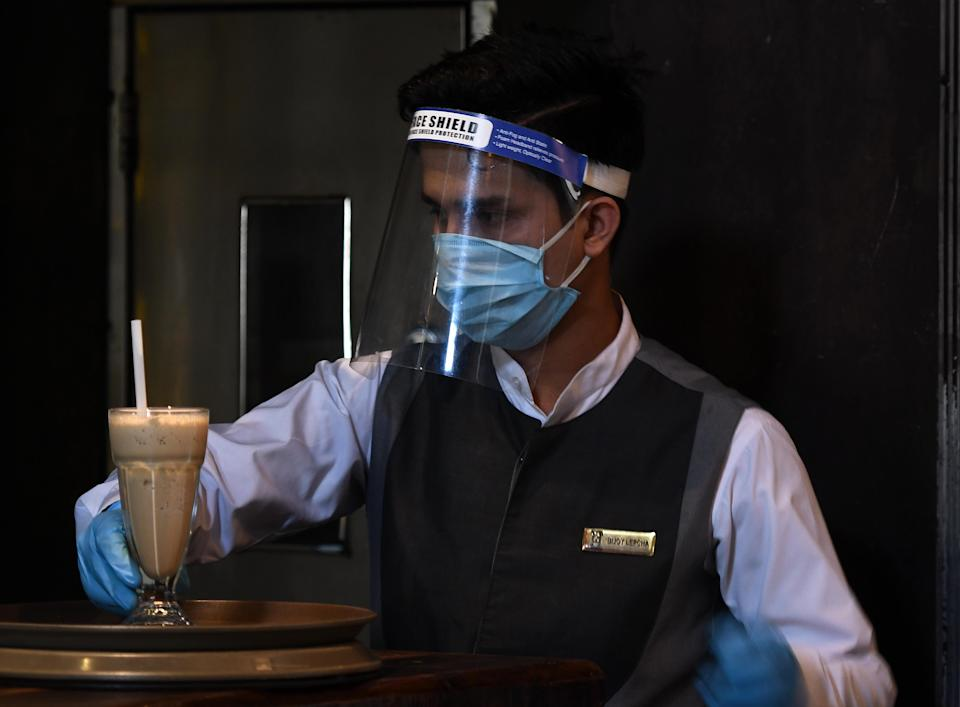 NEW DELHI, INDIA - JUNE 9: A waiter wearing a face mask, gloves and shield at Town Hall restaurant as lockdown restrictions ease at Khan Market on June 9, 2020 in New Delhi, India. (Photo by Biplov Bhuyan/Hindustan Times via Getty Images)