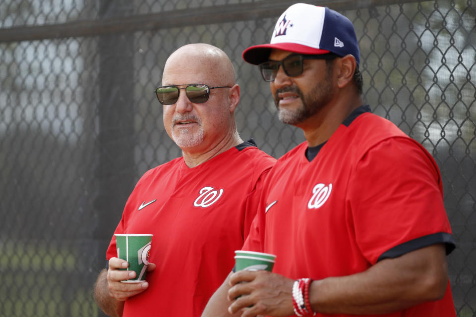 FILE - In this Feb. 17, 2020, file photo, Washington Nationals general manager Mike Rizzo, left, talks with manager Dave Martinez during spring training baseball practice in West Palm Beach, Fla. (AP Photo/Jeff Roberson, File)