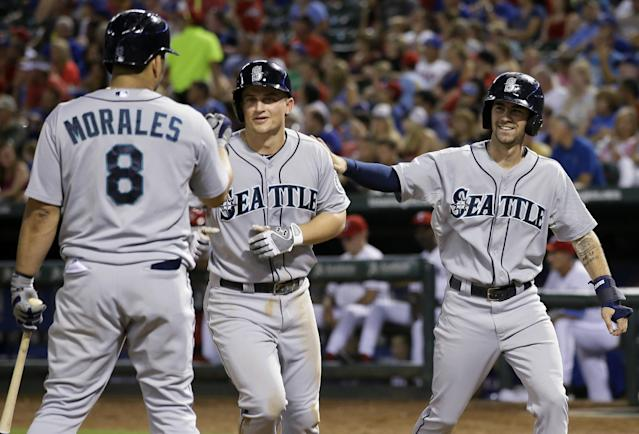 Seattle Mariners' Kendrys Morales (8) and Nick Franklin, right, congratulate Kyle Seager, center, at the plate following Seager's two-run home run off Texas Rangers relief pitcher Neal Cotts that scored Franklin in the eighth inning of a baseball game, Friday, Aug. 16, 2013, in Arlington, Texas. (AP Photo/Tony Gutierrez)