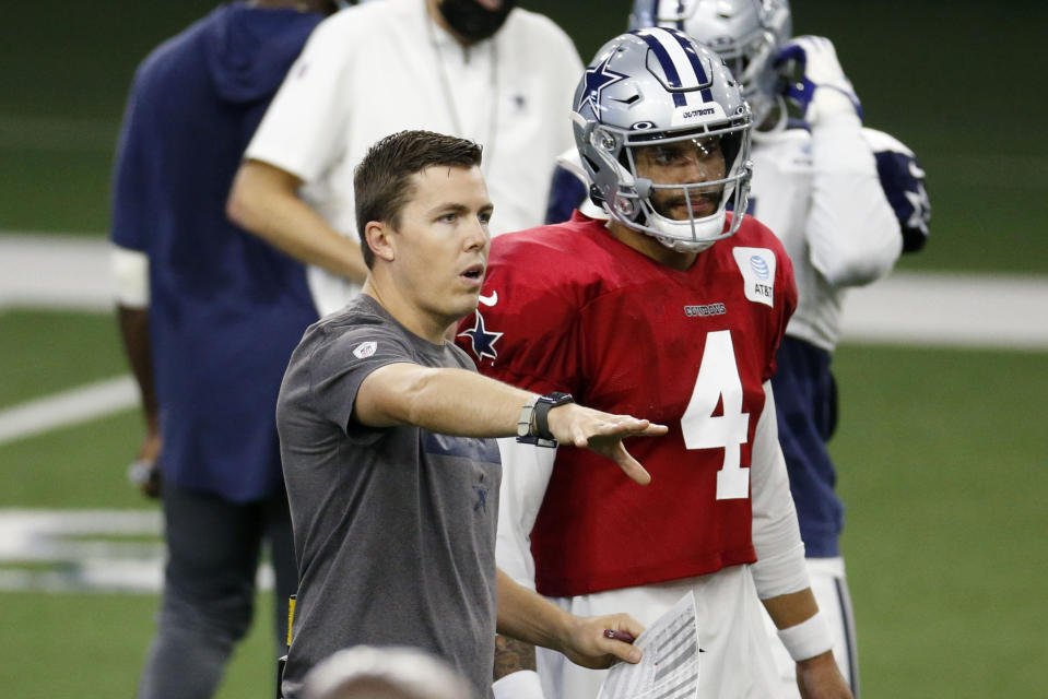Dallas Cowboys offensive coordinator Kellen Moore talks to quarterback Dak Prescott (4) during an NFL football training camp in Frisco, Texas, Sunday, Aug. 23, 2020. (AP Photo/Michael Ainsworth)
