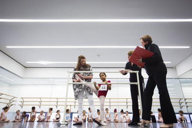 Faculty members check the limberness of a girl during an audition for the School of American Ballet in New York April 25, 2014. The school is holding auditions for over 600 beginner ballet students, who will be selected to fill the 120 spots available to study the dance on campus. REUTERS/Lucas Jackson (UNITED STATES - Tags: SOCIETY EDUCATION)