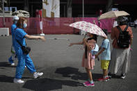 A volunteer sprays water on children as they use umbrellas to beat the heat outside the Fuji International Speedway, the finish for the women's cycling road race that is underway, at the 2020 Summer Olympics, Sunday, July 25, 2021, in Oyama, Japan. (AP Photo/Christophe Ena)