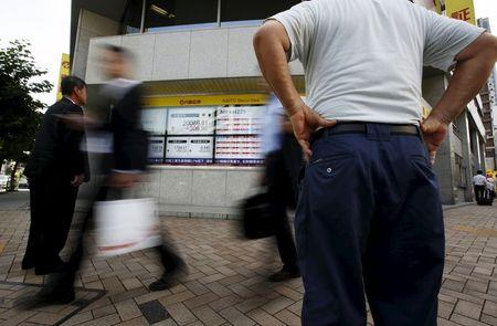 Passersby walk past an electronic stock quotation board outside a brokerage in Tokyo July 13, 2015. REUTERS/Issei Kato