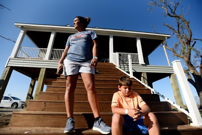 Edie Higgins and her oldest son, Eli Higgins, in front of their house the day after Hurricane Delta in Cameron, Louisiana, on Saturday, Oct. 10, 2020.
