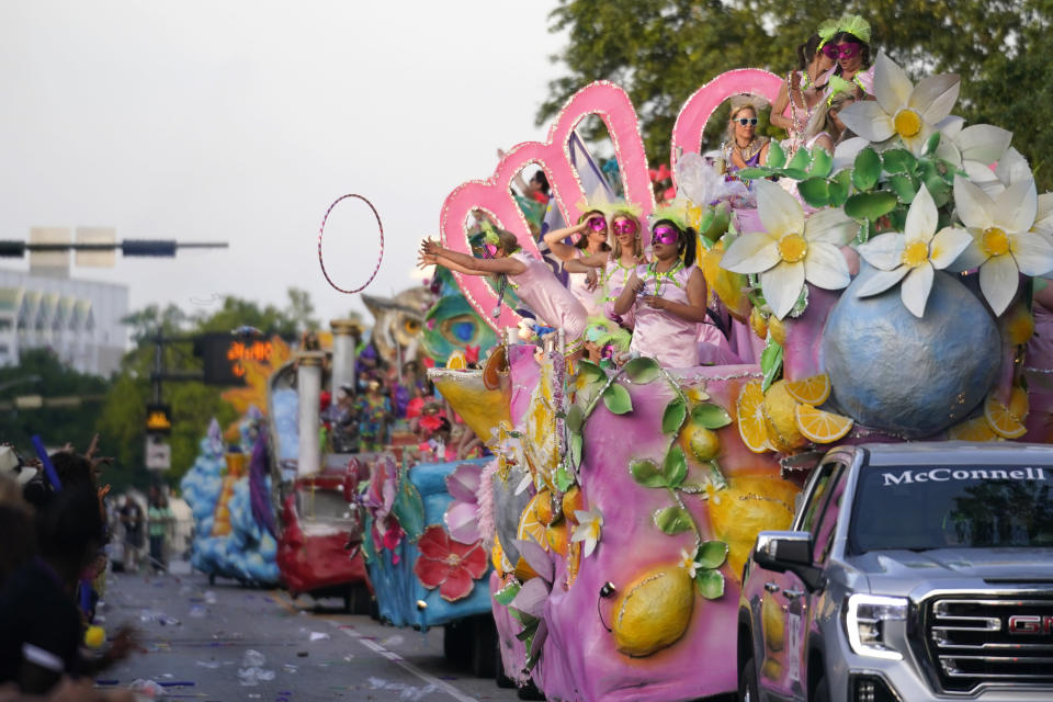 """Riders toss throws from a float during a parade dubbed """"Tardy Gras,"""" to compensate for a cancelled Mardi Gras due to the COVID-19 pandemic, in Mobile, Ala., Friday, May 21, 2021. (AP Photo/Gerald Herbert)"""