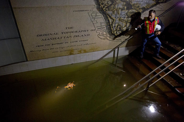 Joseph Leader, Metropolitan Tranportation Authority Vice President and Chief Maintenance Officer, shines a flashlight on standing water inside the South Ferry 1 train station in New York, N.Y., Wednesday, Oct. 31, 2012, in the wake of superstorm Sandy. The floodwaters that poured into New York's deepest subway tunnels may pose the biggest obstacle to the city's recovery from the worst natural disaster in the transit system's 108-year history. (AP Photo/Craig Ruttle)