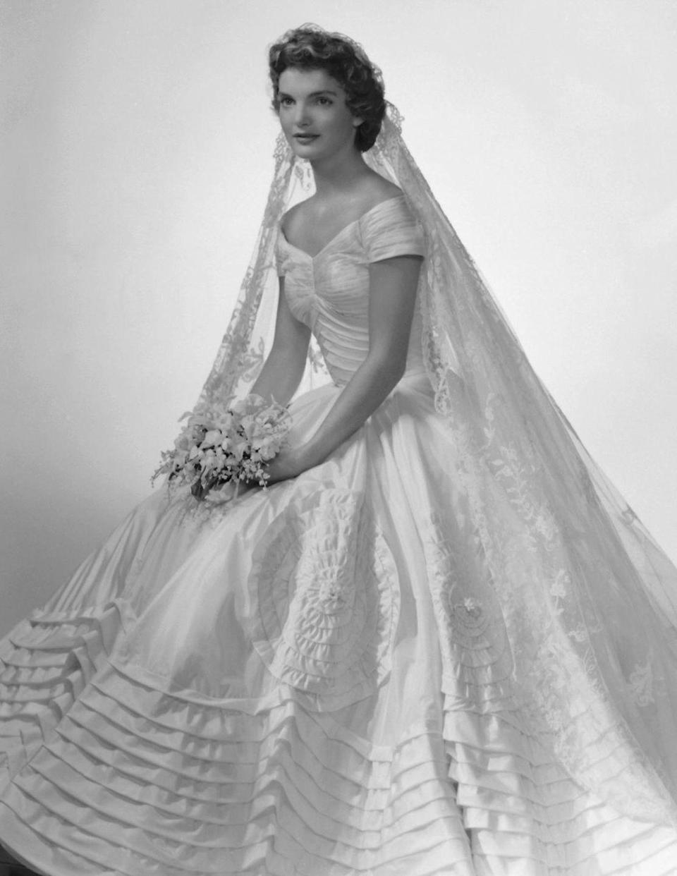 <p>Jackie's original wedding gown was destroyed in a flood, but designer Ann Lowe saved the day with a dress that included a portrait neckline and full skirt.</p>