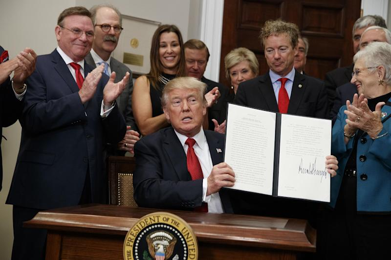 President Donald Trump shows an executive order on healthcare that he signed in the Roosevelt Room of the White House: AP