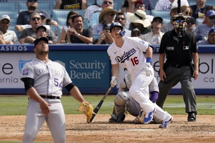 Los Angeles Dodgers' Will Smith, center, runs to first after hitting a solo home run as Colorado Rockies relief pitcher Carlos Estevez, left, watches along with home plate umpire Jerry Meals during the eighth inning of a baseball game Sunday, July 25, 2021, in Los Angeles. (AP Photo/Mark J. Terrill)