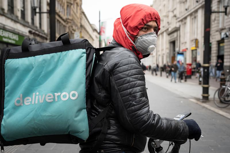 CARDIFF, UNITED KINGDOM - MARCH 14: A Deliveroo rider wears a surgical face mask in Cardiff city centre on March 14, 2020 in Cardiff, United Kingdom. Coronavirus (Covid-19) has spread to over 149 countries in a matter of weeks, claiming over 5,600 lives and infecting nearly 150,000. As of today, there are over 1000 diagnosed cases in the UK and 21 deaths. (Photo by Matthew Horwood/Getty Images)