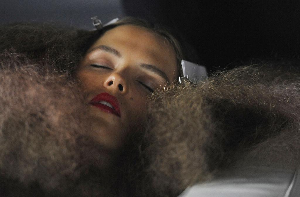 <p>A model uses her brushed-out curlsas a pillow to sleep backstage beforethe Unique spring show duringLondon Fashion Week. (Photo: Getty Images) </p>