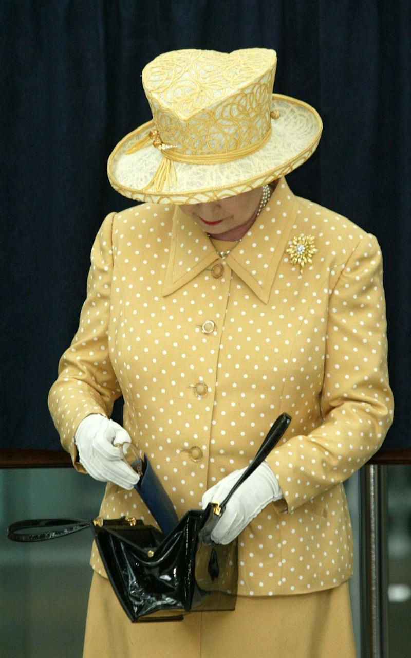 The Queen takes her glasses out of her handbag in Norwich in 2002 - Credit: Ian Jones