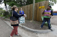 Clinic escort Myles Ray, right, argues with Susan Weiand, an anti-abortion supporter, left, while anti-abortion supporter, Doug Hiser, center, watches, at the Jackson Women's Health Organization clinic, Wednesday, March 25, 2020, in Jackson, Miss. The clinic is Mississippi's only state licensed abortion facility. Weiand is also fearful that patients from out of state might be carriers of the coronavirus and may endanger the community. Gov. Tate Reeves told reporters at a press conference Tuesday that he considers abortion an elective and unnecessary procedure.. (AP Photo/Rogelio V. Solis)