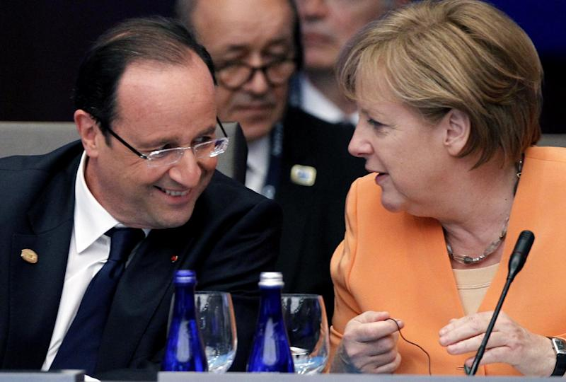 French President Francois Hollande, left, talks with German Chancellor Angela Merkel at the North Atlantic Council meeting in Chicago during the NATO 2012 Summit Sunday, May 20, 2012. French Defense Minister Jean-Yves Le Drian is at back center. (AP Photo/Christophe Ena)