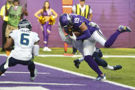 Minnesota Vikings wide receiver Adam Thielen (19) scores a touchdown on a catch in front of Seattle Seahawks strong safety Quandre Diggs (6) in the first half of an NFL football game in Minneapolis, Sunday, Sept. 26, 2021. (AP Photo/Bruce Kluckhohn)