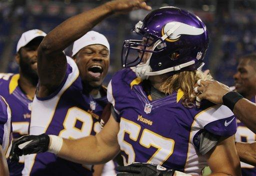 Minnesota Vikings linebacker Audie Cole (57) is congratulated by teammates after scoring on an interception against Buffalo Bills quarterback Vince Young in the second half of an NFL preseason football game, Friday, Aug. 17, 2012, in Minneapolis. The Vikings won 36-14. (AP Photo/Genevieve Ross)