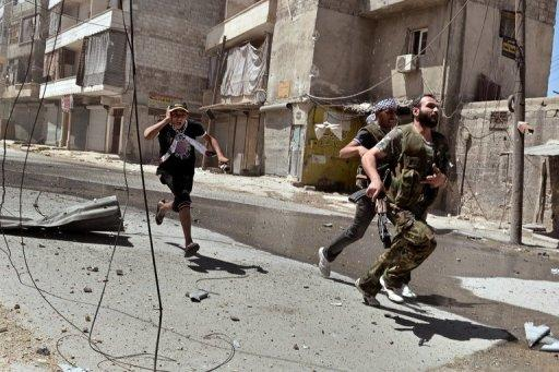 """Rebel fighters run for cover during fighting in the al-Mashad neighbourhood of the northern city of Aleppo on August 25. Dozens of bodies were found as Syrian forces launched a deadly assault in the southwestern belt of Damascus on Saturday, in what activists said was a new bid to crush """"once and for all"""" the insurgency in the capital"""