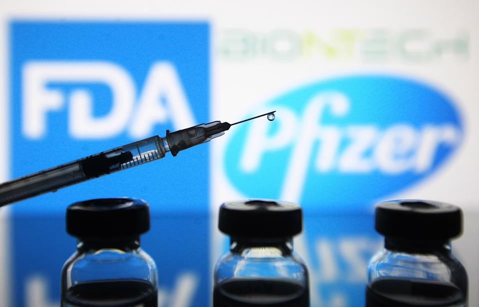 UKRAINE - 2020/12/12: In this photo illustration, vials and a medical syringe seen in front of the Food and Drug Administration (FDA) of the United States and Pfizer Pharmaceutical company logos. FDA approves Pfizer/BioNTech the COVID-19 coronavirus vaccine for emergency use in the US, reportedly by media. (Photo Illustration by Pavlo Gonchar/SOPA Images/LightRocket via Getty Images)