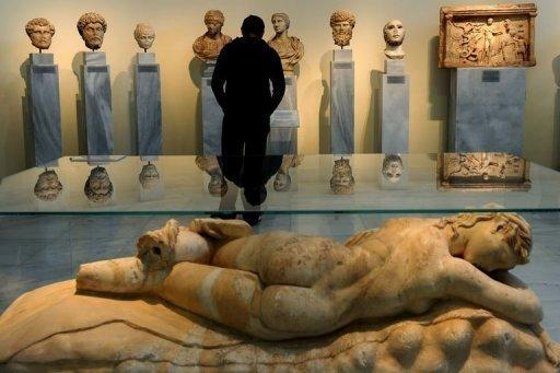 "A visitor looks at antiquities at the National Archeological Museum in Athens on March 18, 2012. Faced with huge public debt as it moves into a fifth year of recession, Greece is finding that its fabled antiquity heritage is proving a growing burden. ""Greece's historic remains have become our curse,"" whispered an archaeologist worried about budgets that are badly stretched to nonexistent"