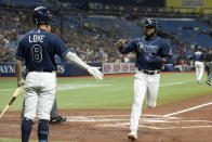 Tampa Bay Rays' Manuel Margot, right, heads to the dugout and is congratulated by Brandon Lowe after scoring during the first inning of the team's baseball game against the Detroit Tigers on Thursday, Sept. 16, 2021, in St. Petersburg, Fla. (AP Photo/Scott Audette)