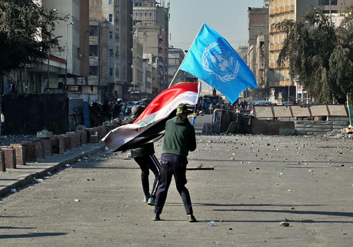 Anti-government protesters wave national and U.N. flags during clashes with security forces in Baghdad, Iraq, Friday, Jan. 31, 2020. (AP Photo/Hadi Mizban)