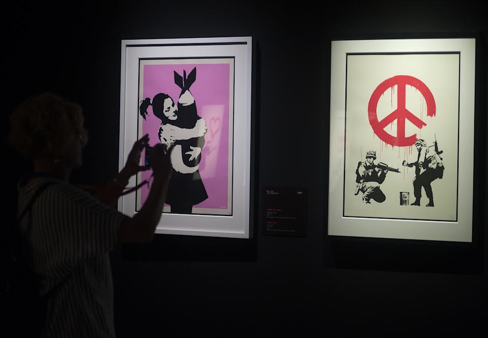 """A woman seen taking photos of a painting during the exhibition 'Banksy The art of Protest' at cultural center 'La T�rmica' is an exhibition showing for the first time in Malaga. the work of famous and mysterious British street artist 'Banksy', display more than 40 creations such originals works, sculptures, videos and photographs provide by international private collections including the original print of """"Ni�a con globo"""". (Photo by Jesus Merida Luque / SOPA Images/Sipa USA)"""