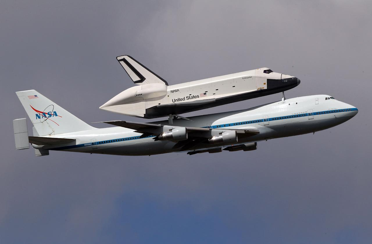 NEW YORK, NY - APRIL 27:  Space shuttle Enterprise, mounted atop a 747 shuttle carrier aircraft, flies past Jersey City prior to landing at John F. Kennedy International Airport on April 27, 2012 in New York City. Enterprise, which was flown from Washington, DC, will eventually be put on permanent display at the Intrepid Sea, Air and Space Museum.  (Photo by Michael Heiman/Getty Images)