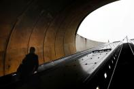 FILE PHOTO: A person descends down an escalator during commuter evening rush hour, at the Dupont Circle Metro underground train station, as Mayor Muriel Bowser declared a State of Emergency due to the coronavirus disease (COVID-19) in Washington