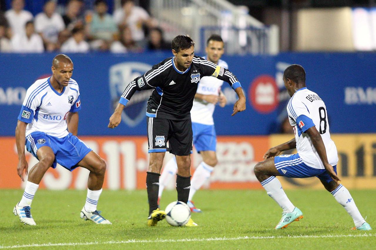 MONTREAL, CANADA - AUGUST 18:  Chris Wondolowski #8 of the San Jose Earthquakes moves the ball past Patrice Bernier #8 and Matteo Ferrari #13 of the Montreal Impact during the match at the Saputo Stadium on August 18, 2012 in Montreal, Quebec, Canada.  The Impact defeated the Earthquakes 3-1.  (Photo by Richard Wolowicz/Getty Images)